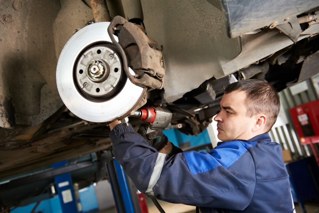 car mechanic examining car suspension