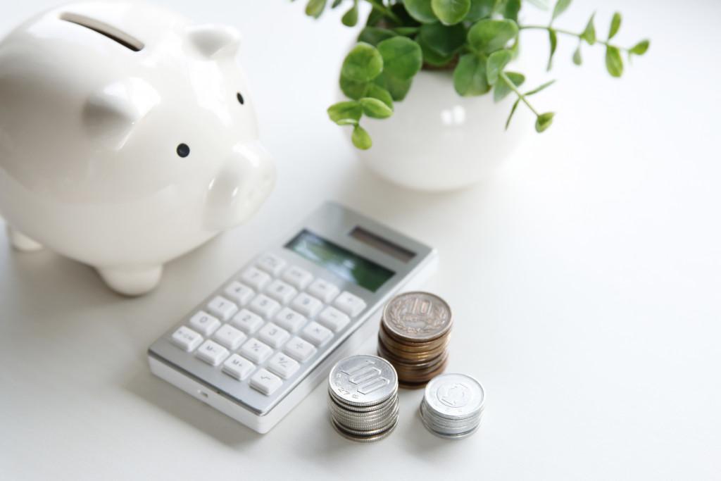 white piggybank, calculator, and coins
